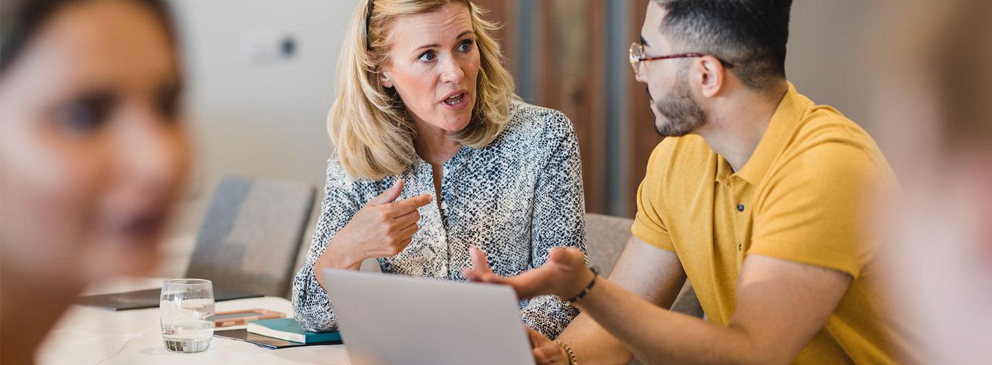 En kvinna och en man sitter bredvid varandra och diskuterar vid ett möte.