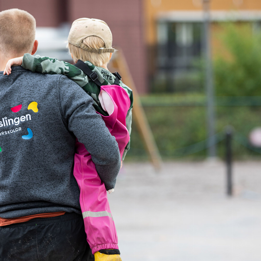 Vuxen som håller upp ett barn i en skolgårdsmiljö. Vuxens tröja står det