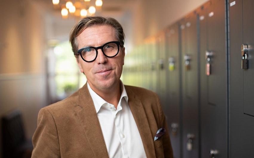 Porträttbild av AcadeMedias VD och Koncernchef , Marcus Strömberg i en skolkorridor.