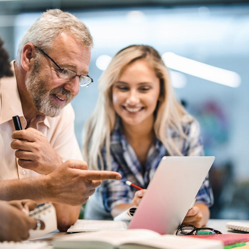 Tre personer sitter på rad i ett möte, en man verkas intresserad av det hans kollega visar honom på hennes surfplatta