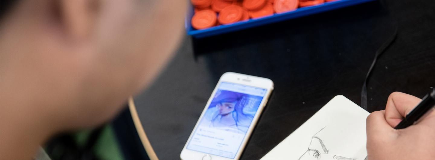 Person som sitter och ritar utifrån en referens på deras mobil
