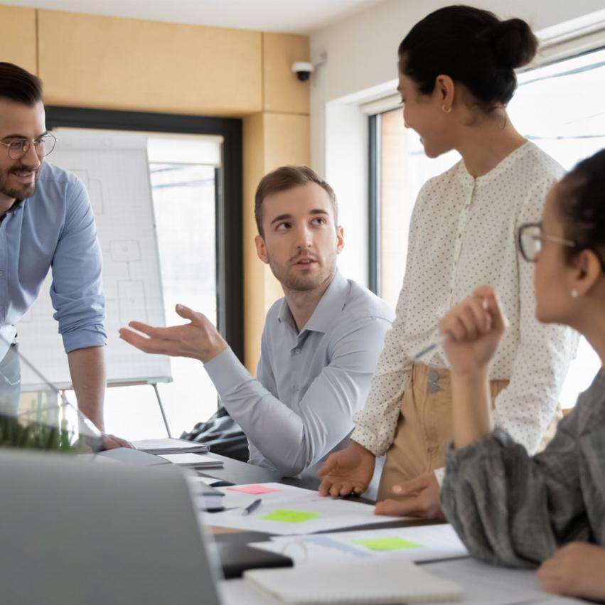 Flera personer sitter i ett litet konferensrum och har möte, de diskuterar och har färgade papperslappar på bordet