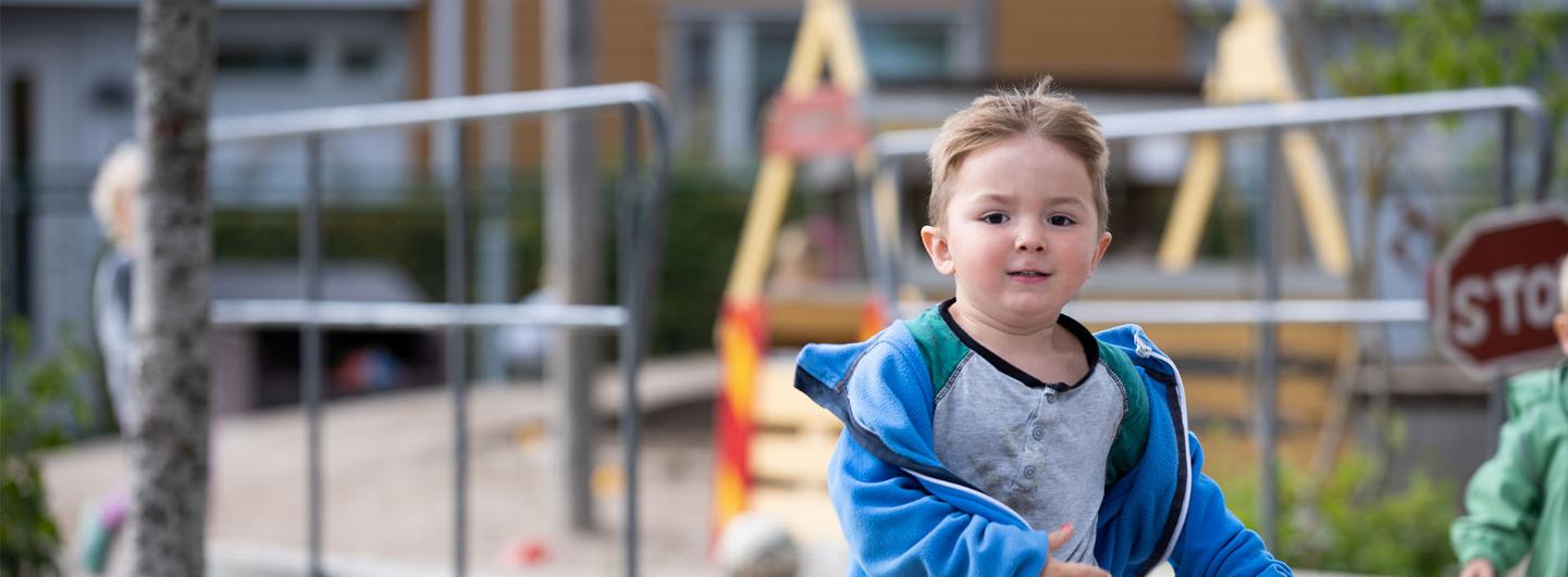 Litet barn springer mot kameran i skolgård