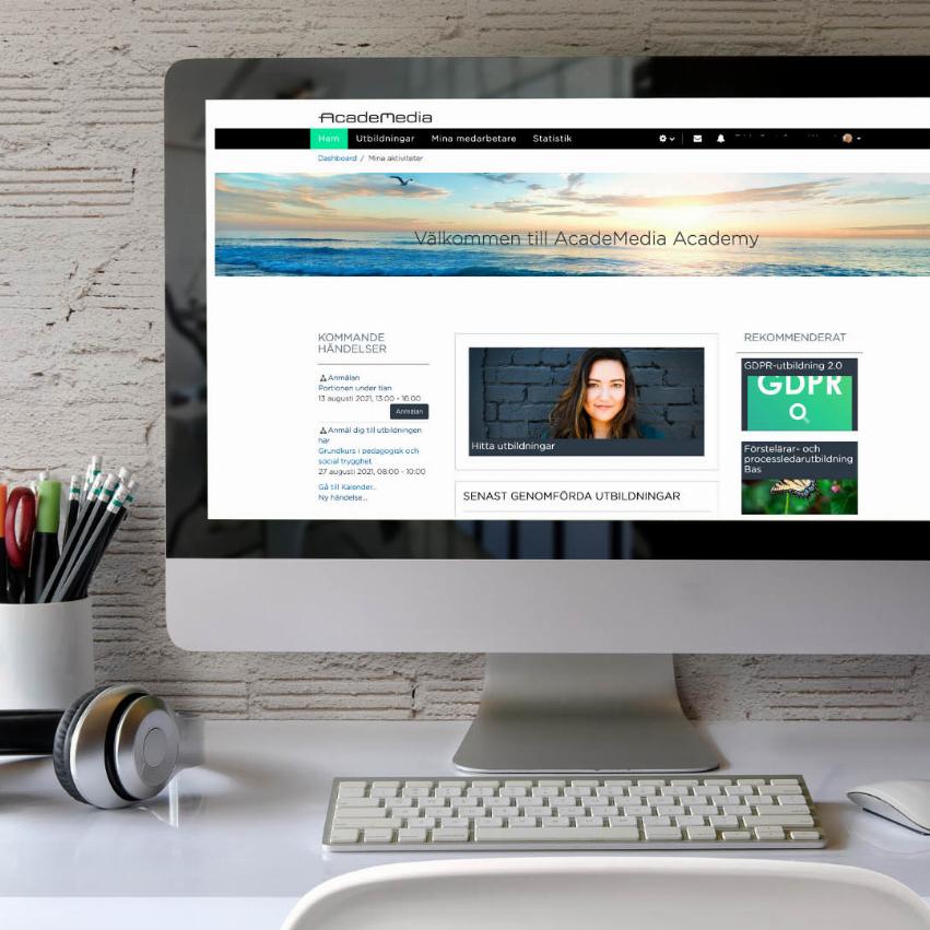 Stationär dator vid en minimalistisk skrivbord. På datorskärmen är AcadeMedias hemsida