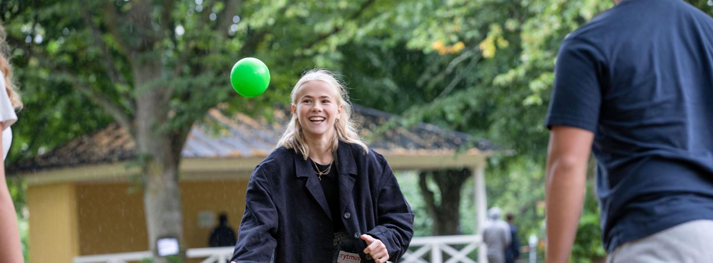 Tjej ska fånga en grönboll, hon står utomhus och har en nyckel band som står