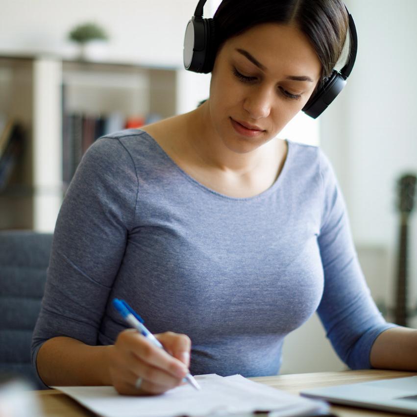 Tjej som pluggar i en biblioteks miljö, hon lyssnar på musik och skriver samtidigt som hon gör det på hennes laptop
