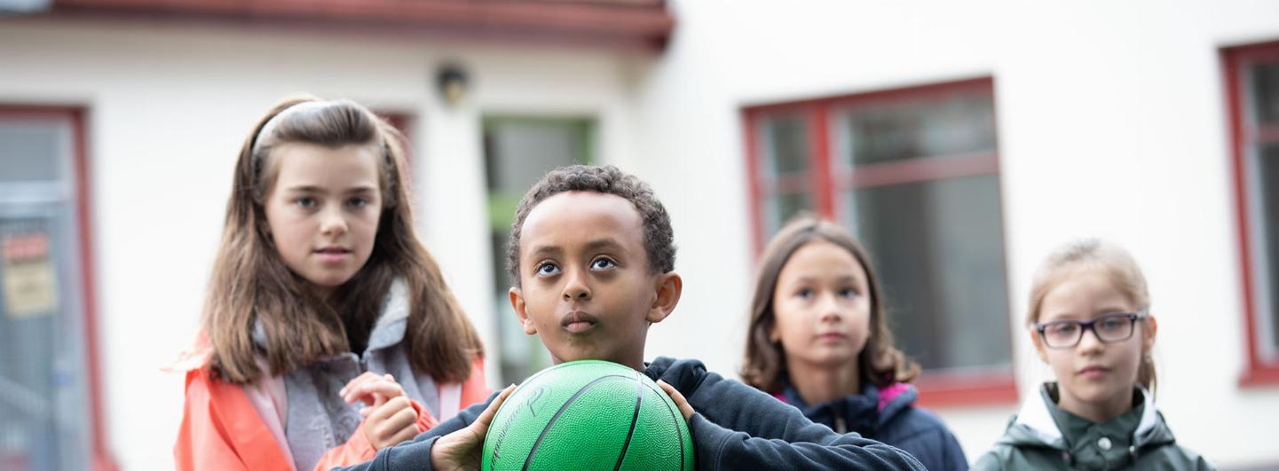 Pojke i centrum som fokuserar på kasta sin gröna basketboll, bakom honom är tre barn som tittar på