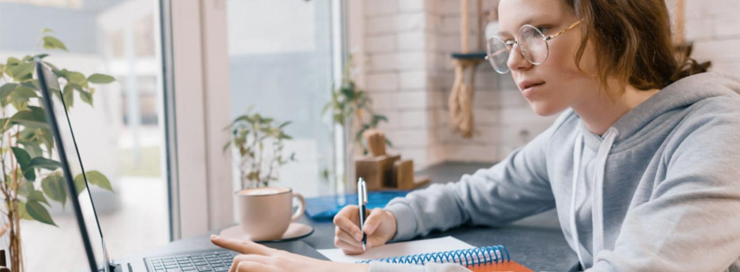Person som pluggar, skriver och tittar på hennes dator