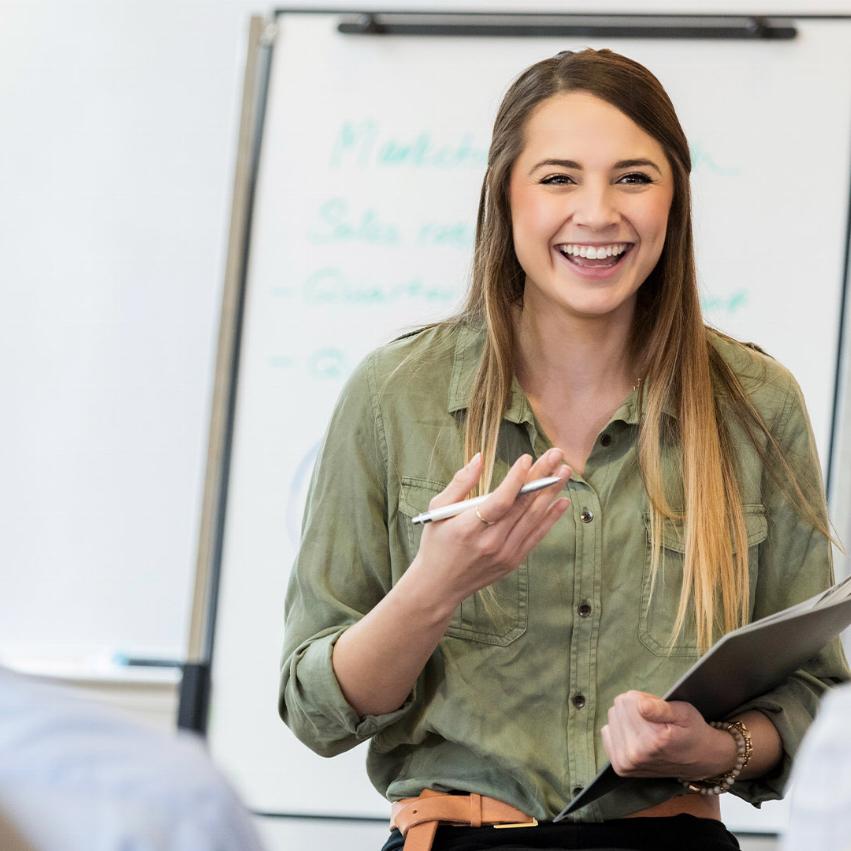 Glad kvinnlig lärare står i ett klassrum och undervisar elever på vux
